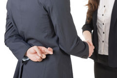 Fake hand shake. Business women and men shake hands and put finger cross on back, closeup portrait isolated on white background Stock Images