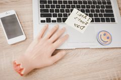 Fake Hand and Smiley Face near Laptop on Table. royalty free stock images