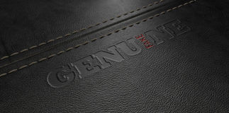 Fake Leather Conterfeit. A stitched sheet of black leather with an embossed stamp reading genuine but the one letter reads the word fake stock images