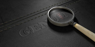 Fake Leather With Magnifying Glass. A stitched sheet of black leather with an embossed stamp reading genuine but magnified by a magnifying glass the one letter stock photo