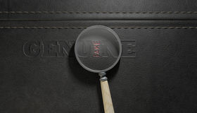 Fake Leather With Magnifying Glass. A stitched sheet of black leather with an embossed stamp reading genuine but magnified by a magnifying glass the one letter Royalty Free Stock Photos