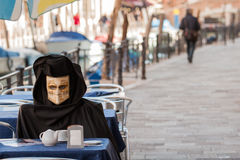 A fake mask have breakfast in venice. Fake mask having breakfast in venice during carnival Stock Image