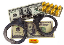 Fake medicines. tablets, handcuffs and dollar bills. illegal med Royalty Free Stock Photo