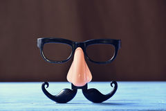 Fake mustache, nose and eyeglasses on a blue surface Royalty Free Stock Photos