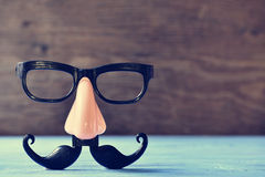 Fake mustache, nose and eyeglasses on a blue surface. A fake mustache, nose and eyeglasses on a rustic blue wooden surface Stock Photos