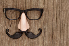 Fake mustache, nose and eyeglasses on a wooden surface. A fake mustache, nose and eyeglasses on a rustic wooden surface stock photo