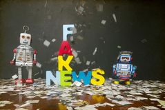 Fake new concept. Newspaper confetti comes down on the word FAKE NEWS  with two retro robot toys on a wooden floor Royalty Free Stock Image