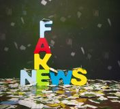 Fake new concept. The word FAKE NEWS on a wooden floor with newspaper confetti Royalty Free Stock Image