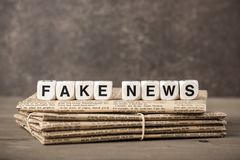 Fake News concept with newspapers and cubes with letters royalty free stock photography