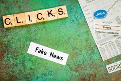 Fake News concept suggesting more clicks make more money. With news items cut out on board royalty free stock photos