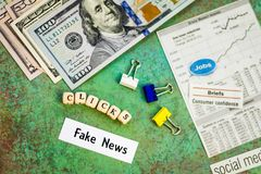 Fake News concept suggesting more clicks make more money. With news items cut out on board stock image