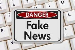 Fake news on Internet danger sign. Fake news danger sign, A black and white danger sign with text Fake News on a keyboard Stock Images