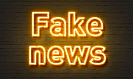 Fake news neon sign on brick wall background. Royalty Free Stock Images