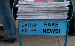 Fake News. Newspaper stack - take one of these newspaper in the subway entrance with headline fake news Stock Photography