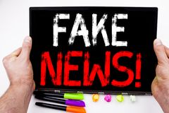 Fake News text written on tablet, computer in the office with marker, pen, stationery. Business concept for Propaganda Newspaper F. Ake News white background Royalty Free Stock Photos