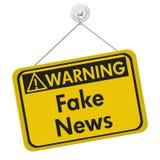 Fake news warning sign isolated on white. Fake news warning sign, A yellow warning hanging sign with text Fake News isolated over white Stock Images