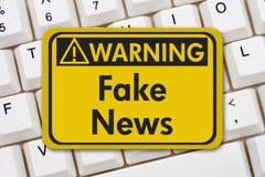 Fake news warning sign on keyboard. Fake news warning sign, A yellow warning sign with text Fake News on a keyboard Stock Image
