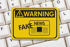 Fake News warning sign. A yellow warning sign with text Fake News on a keyboard Stock Photo