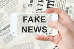 Fake news written on a computer smartphone screen, newspapers background stock photo