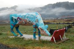 Fake Cow grazes near Oregon's Coast Range. This is a fake painted cow grzing with Oregon's Cascade Range covered with mist in the background stock images