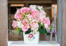 Fake pink rose bouquet in white vase. Decorating on wooden frame Royalty Free Stock Images