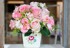 Fake pink rose bouquet in white vase. Decorating on wooden frame Stock Photo