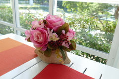 Fake pink rose on white table near window with garden view. Bouquet of fake pink rose in sack bag on white wooden table near window with garden view Royalty Free Stock Images