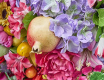 Fake pomegranate and flowers closeup Stock Images