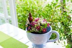 Fake purple flower in blue ceramic cup on white wooden table nea. R the window with garden view Stock Image