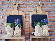 Fake purple flowers on wooden shelf. Artficial fake purple flowers on wooden shelf hanging on brick wall in coffee cafe. Antique decoration in pastel vintage royalty free stock photography