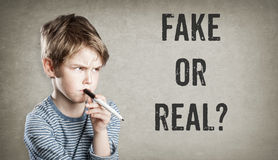 Fake or real, Boy on grunge background. Fake or real, Boy considering the question, on grunge background, writing and thinking, copy space Stock Images
