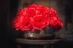 Fake red roses in shadows on a metallic pot - valentine's day Stock Images