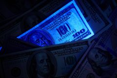 Fake us dollar bill in UV light. Closeup Stock Images
