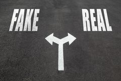 Fake vs real choice concept. Two direction arrows on asphalt Stock Photo