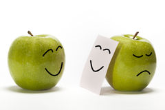 Fakeing feelings. An apple smiling to other one, that is concealing its sadness behind a smily mask Stock Images