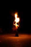 Fakir. Fire-eater performance on a street and audience on a dark background Stock Images