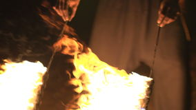 Fakir spining burning ropes in front of his legs. Fire show performance at night. Slow motion stock footage
