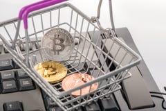Faktisk myntbitcoin i shoppingvagn på det för- tangentbordet som är trad Royaltyfri Foto