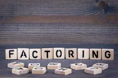 faktor bei Wort darstellen geschrieben auf hölzernen Block Dunkler hölzerner Hintergrund mit Beschaffenheit Lizenzfreies Stockfoto