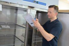 Faktotum som hemma kontrollerar kylskåpet arkivfoton