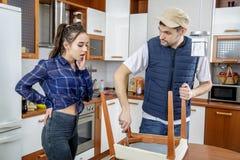Faktotum som reparerar möblemang i köket Han reparerar en stol med en skruvmejsel Royaltyfria Bilder