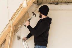 Faktotumanseende på en stege och renovera ett hem, genom att använda hjälpmedel som en hammare fotografering för bildbyråer