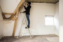 Faktotumanseende på en stege och renovera ett hem, genom att använda hjälpmedel som en hammare arkivfoto
