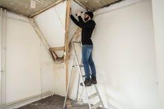 Faktotumanseende på en stege och renovera ett hem, genom att använda hjälpmedel som en hammare arkivbild