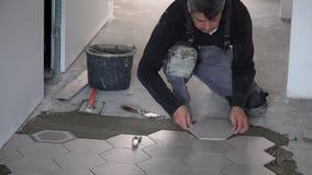 Faktotumet lägger att tendera sexhörningstegelplattor på golv i korridor arkivfilmer