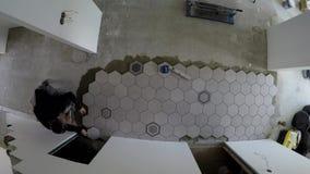 Faktotumet l?gger att tendera sexh?rningstegelplattor p? golv i korridor Timelapse stock video