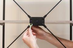 Faktotumet tillfogar bokhyllakonstruktionen, genom att skruva bultarna med en sexhörnig skiftnyckel Royaltyfria Foton