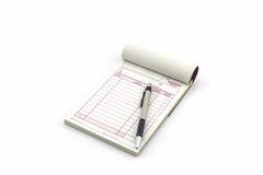 Fakturabok som öppnar den tomma sidan med pennan Arkivbild