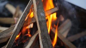 Falò con una forte fiamma nella forma di capanna in cui mette il bordo nell'inverno archivi video