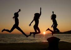Falò, sorelle che saltano nel tramonto Immagine Stock